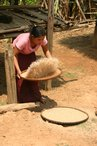 One of the local girls preparing the rice for pounding